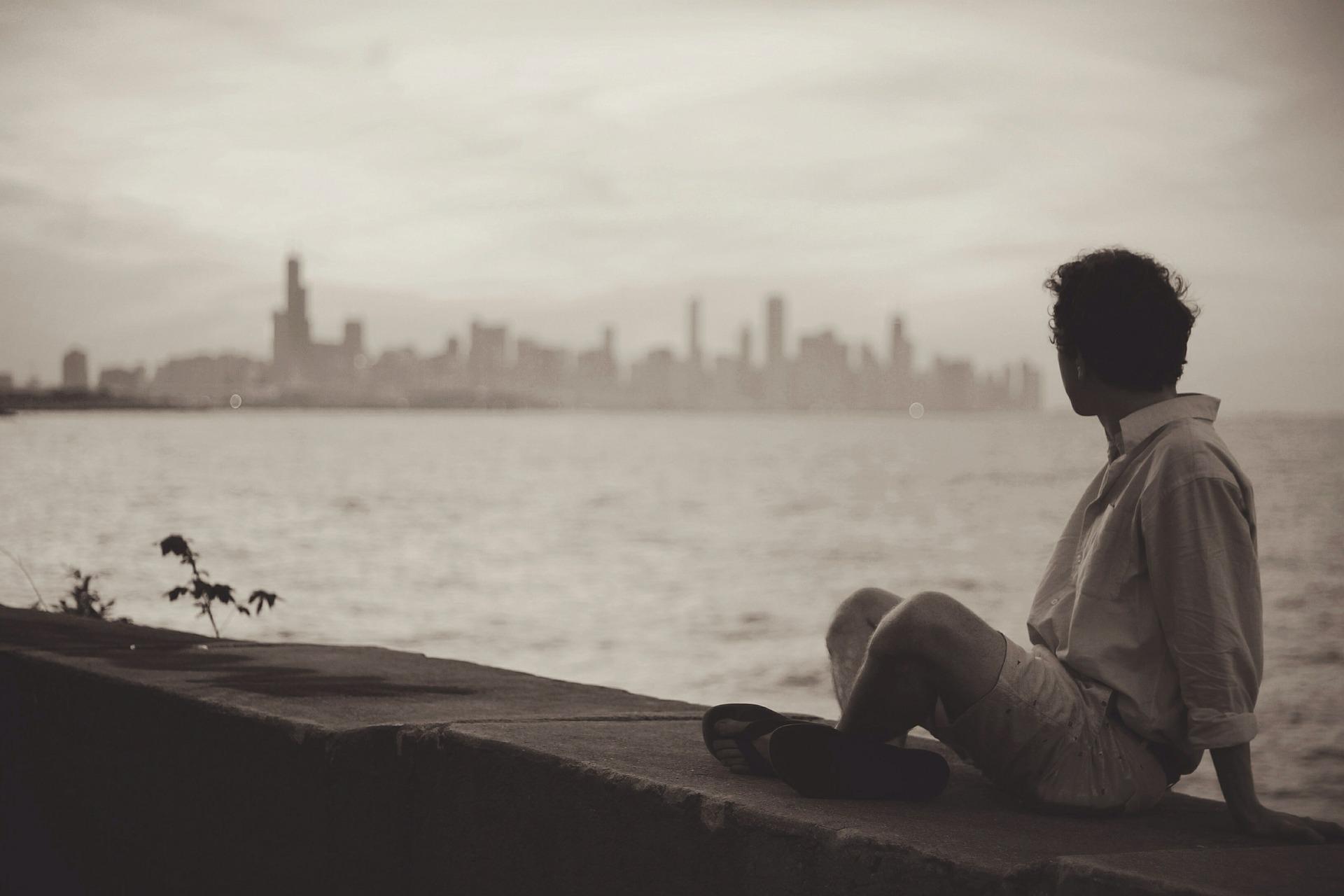 man sitting by water skyline