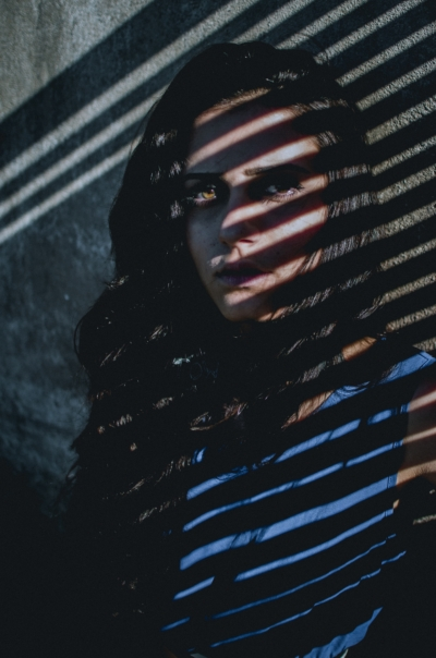 girl in shadows of blinds