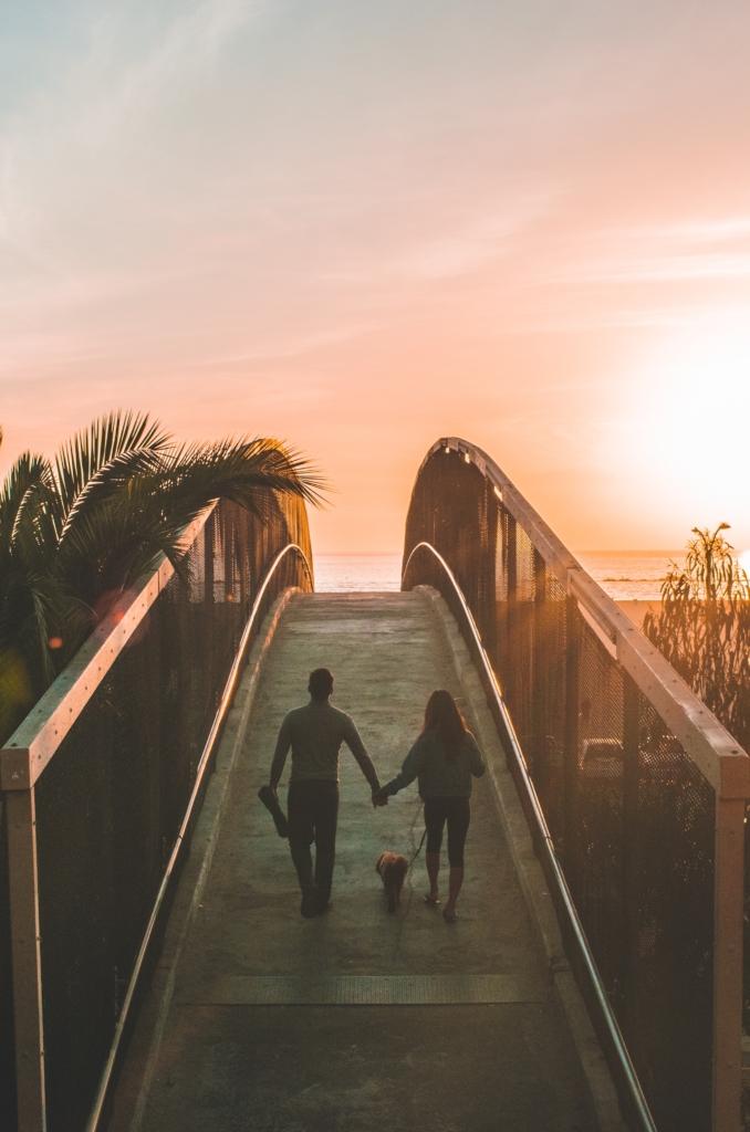 couple walking on bridge dog