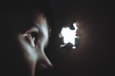 child peeking through hole