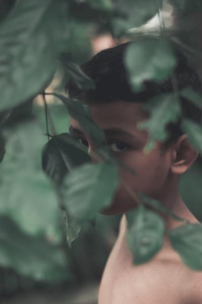 boy hiding leaves