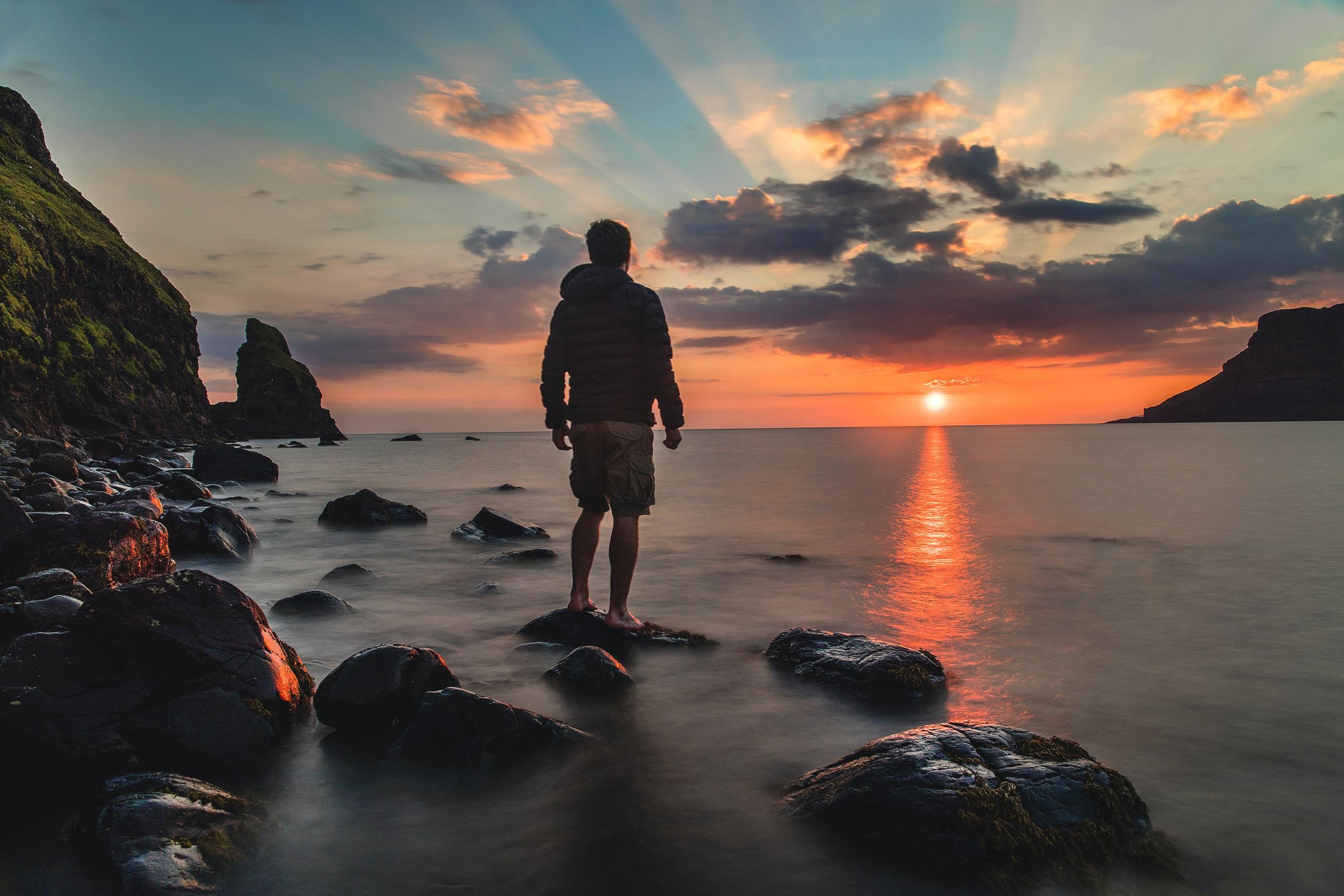man at sunset on rock
